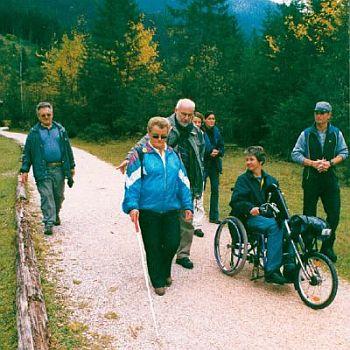 Eine Gruppe von zum Teil behinderten Menschen beim Wander auf einem gut ausgebauten Weg