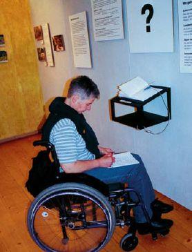 Rollstuhlfahrer vor einem Ausstellungsstück