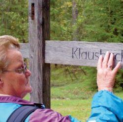 Blinde Naturfreundin tastet auf einem Hinweisschild