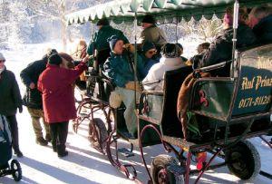 Eine voll besetzte Pferdekutsche in einer Winterlandschaft