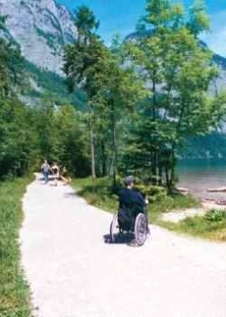 Ein Rollstuhlfahrer auf einem gut ausgebauten Weg am Seeufer