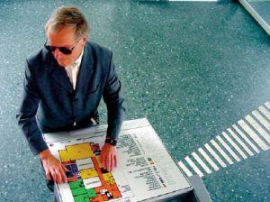 Eine blinde Person tastet auf einer Orientierungstafel