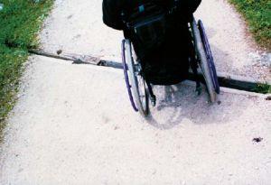 Rollstuhlfahrer, der über eine breite Querfuge fährt